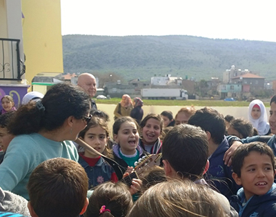 A friend sings with the kids at the school, I'm in the background and the hills of Syria in the background.